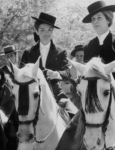 23 Apr 1966, Seville, Spain --- Jacqueline Kennedy rides a horse beside another woman at the spring fair in Seville. The two wear typical Andalusian riding outfits. --- Image by © Bettmann/CORBIS